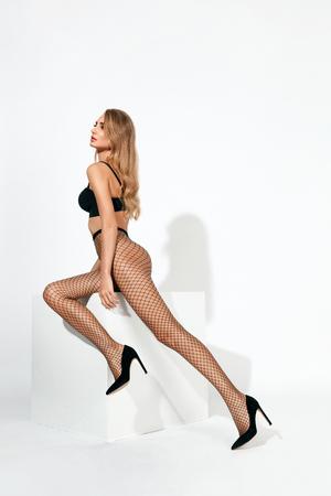 Sexy Frau in schwarzen Netzstrumpfhosen . Schöne Frau mit fit Körper in Strümpfen auf langen Beinen . Hohe Auflösung Standard-Bild - 101018426