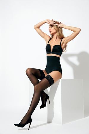 Medias negras. Mujer hermosa joven con las piernas largas en lencería sexy sobre fondo blanco. Alta resolución.