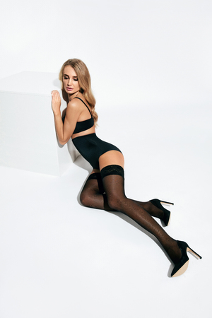 Sexy Female In Stylish Stockings And Black Lingerie On White Background. High Resolution. 版權商用圖片