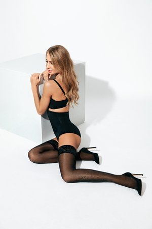 Sexy Female In Stylish Stockings And Black Lingerie On White Background. High Resolution. Archivio Fotografico