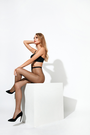 Sexy Woman In Black Fishnet Tights. Beautiful Female With Fit Body In Stockings On Long Legs. High Resolution. Stockfoto