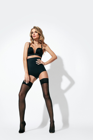Black Stockings. Young Beautiful Woman With Long Legs In Sexy Lingerie On White Background. High Resolution.
