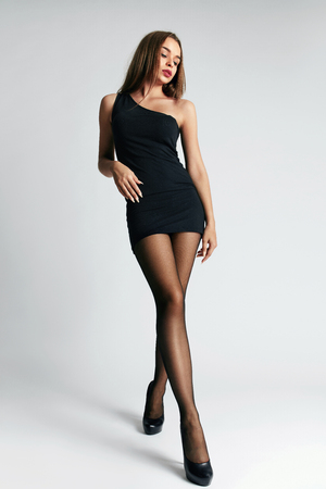 Beautiful Woman With Long Legs And Sexy Body In Black Stylish Dress And Stockings. High Resolution.