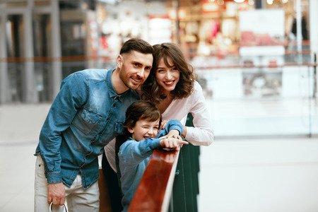 Happy Family Shopping. Young Parents And Smiling Child Having Fun In Mall. High Resolution. Stockfoto