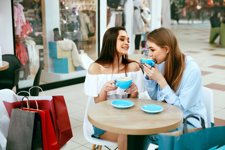 Girls Friends Drinking Coffee In Cafe, Speaking And Laughing While Sitting At Table In Shopping Mall. High Resolution.