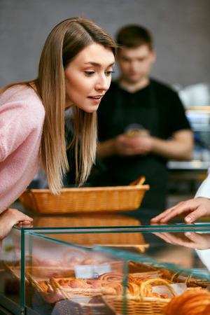 Pastry. Beautiful Woman Choosing Fresh Bakery In Shop. High Resolution.