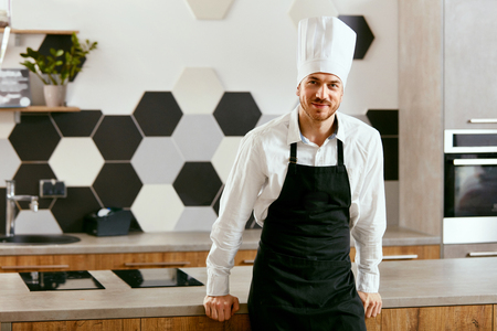 Young Cook In Modern Kitchen. Portrait Of Handsome Chef In Apron And White Hat. High Resolution.