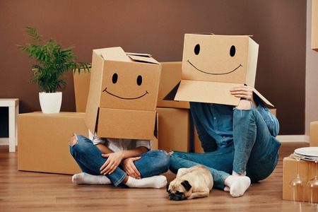Funny Couple With Cardboard Boxes On Heads With Smiley Face Sitting On Floor With Dog In New Home. High Resolution. Stock Photo