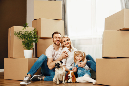 Family Moving Home. Happy People With Child And Dog Hugging While Sitting On Floor In New House. High Resolution. Stockfoto