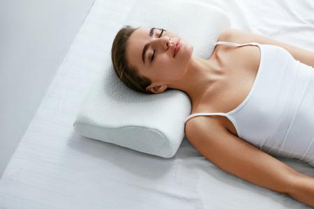 Gesunder Schlaf. Frau, die auf weißem orthopädischem Kissen im Bett schläft. Hohe Auflösung.
