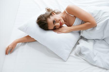 Mujer en la cama, acostado en ropa de cama blanca con almohada y manta. Alta resolución. Foto de archivo
