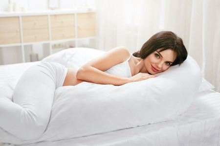 Pregnancy Pillow. Pregnant Woman Resting On Body Pillow Lying On White Bed. High Resolution