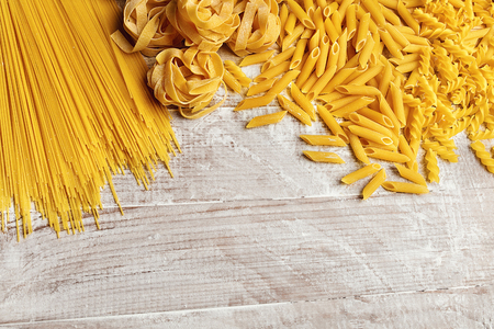 Different Pasta Types On Wooden Table Close Up. Food Background. High Resolution Stock Photo