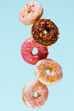 Donuts. Doughnuts On Blue Background. Sweet Colorful Pastries Falling Or Flying In Motion. High Resolution Banco de Imagens
