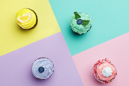Cupcakes Desserts On Colorful Background. Cakes With Different Colors Cream And Toppings. High Resolution
