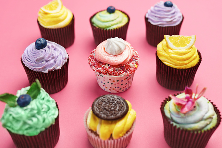 Colorful Cupcakes On Pink Background. Cake Desserts With Cream And Different Toppings. High Resolution 免版税图像