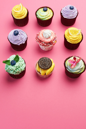 Colorful Cupcakes On Pink Background. Cake Desserts With Cream And Different Toppings. High Resolution 版權商用圖片