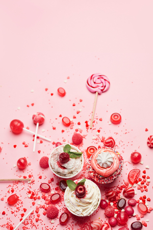 Sweets. Candy And Cupcakes On Pink Background. Red And Pink Candies And Cakes Closeup. High Resolution
