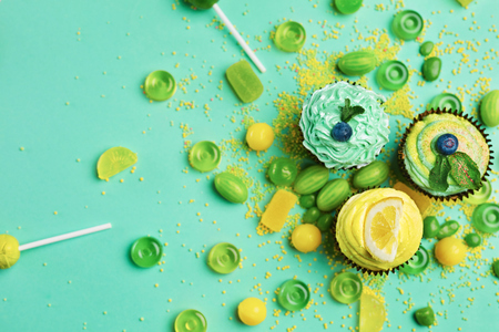 Cupcakes And Candies. Sweets And Desserts On Green Background. High Resolution