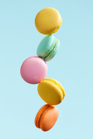 Macaron Biscuit. Colorful Macaroons Flying. French Dessert In Motion Falling On Blue Background. High Resolution