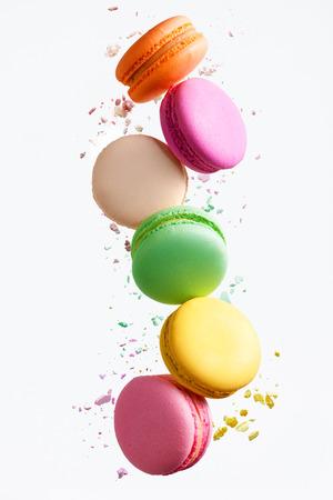 Dulces Macaron. Macarrones coloridos volando. Postre francés en movimiento cayendo sobre fondo blanco. Alta resolución Foto de archivo