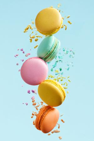 Macaron Dessert. Bunte Makronen fliegen. Französisches Dessert in Bewegung, das auf blauen Hintergrund fällt. Hohe Auflösung