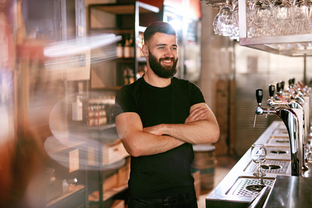 Bartender In Beer Pub. Portrait Of Young Man Standing At Bar Counter. High Resolution.