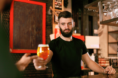Bartender With Draught Beer In Glass In Bar. Smiling Man Working In Pub. High Resolution.