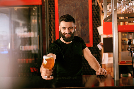 Craft Beer. Man Holding Glass With Beer In Pub, Bartender At Bar Counter. High Resolution. Zdjęcie Seryjne
