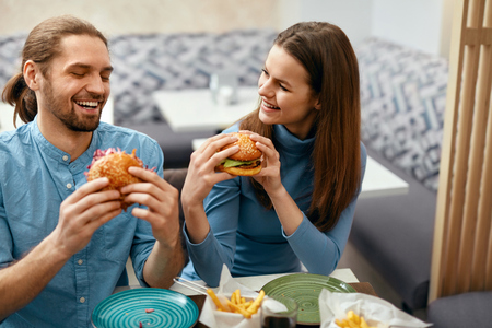 People Having Dinner, Eating Burgers At Cafe. Friends Eating Fast Food In Restaurant. High Resolution.