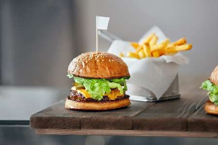 Burger. Close Up Of Tasty Hamburger With Meat, Lettuce And Cheese On Table In Fast Food Cafe. High Resolution. Stockfoto