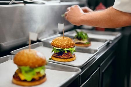 Burger Restaurant. Nahaufnahme Chef, der Burger in der Küche kocht. Hohe Auflösung.