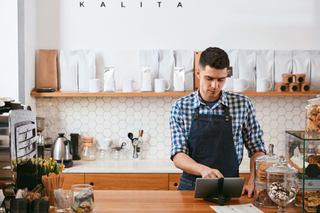 Young Barista Working On Tablet In Cafe, Standing Near Workplace. High Resolution.