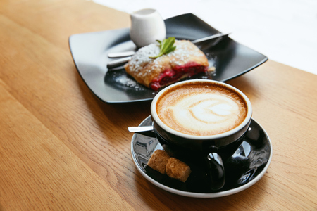 Cup Of Coffee And Tasty Dessert In Cafe. Fresh Hot Drink With Bakery On Wooden Table. High Resolution.