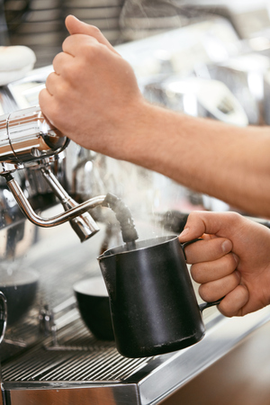 Barista Preparing Coffee On Coffee Machine Closeup, Steaming Milk In Cup In Cafe. High Resolution.