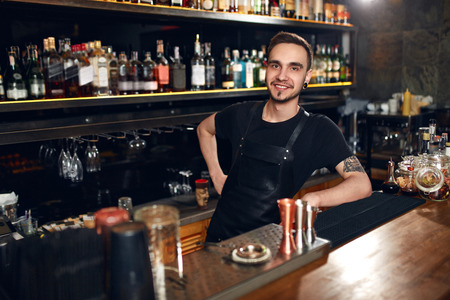 Bartender At Cocktail Bar. Portrait Of Young Barman At Work Standing At Bar Counter. High Resolution Stock Photo