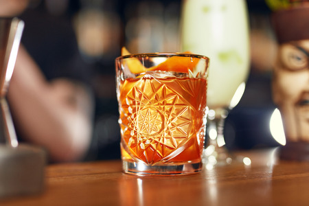 Cocktail Drink In Bar Close Up. Old Fashioned Cocktail With Orange Peel Garnish Bar Counter. High Resolution
