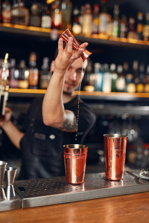 Cocktail. Bartender Making Cocktails in Bar. Barman Making Drinks Using Jigger And Shaker At Bar Counter. High Resolution