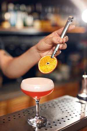 Preparing Cocktails. Bartender Making Clover Club, Sour Cocktail In Bar Decorating It With Dried Orange Slice. High Resolution.