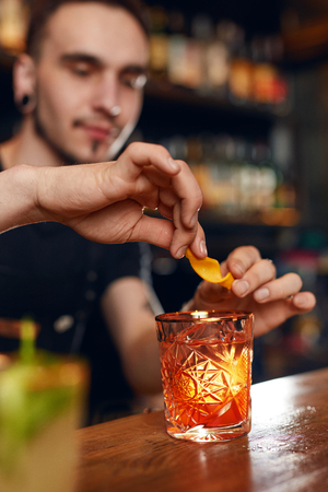 Cocktail. Bartender Preparing Cocktail In Bar. Barman Garnishing Old Fashioned Cocktail With Orange Peel. High Resolution
