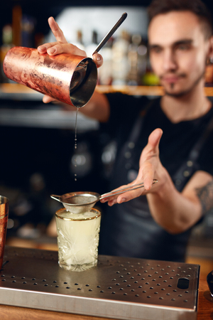 Cocktail Bar. Bartender Making Cocktails, Pouring Drink In Glass. Barman Using Shaker And Sieve. High Resolution