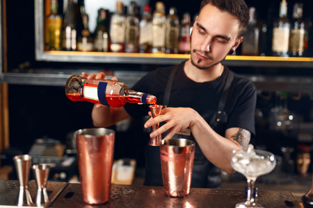 Bar. Bartender Making Cocktails, Measuring Alcohol From Bottle Into Jigger, Mixing Spirits With Cocktail Shaker. High Resolution Stock Photo