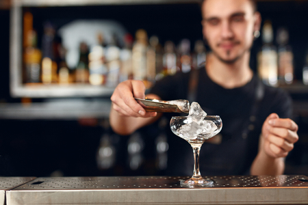 Bartender Making Cocktail. Barman Putting Ice In Glass, Preparing Cocktails At Bar Counter. High Resolution Stock Photo