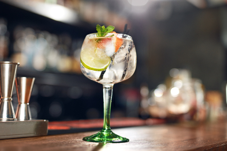Cocktail Drink In Bar Close Up. Glass Of Gin Tonic Cocktail With Lime And Mint On Bar Counter. High Resolution