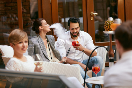 People Smoking Shisha, Drinking Cocktails In Hookah Bar. Couple Smoke And Drink In Restaurant. High Resolution Stock Photo - 112824059