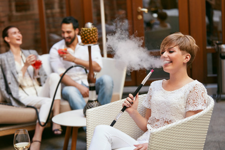 People Smoking Shisha, Drinking Cocktails In Hookah Bar. Couple Smoke And Drink In Restaurant. High Resolution Stock Photo