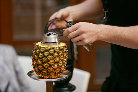 Preparation Pineapple Hookah In Shisha Bar. Mans Hands Preparing Fruit Shisha Cup, Changing Charcoal. High Resolution