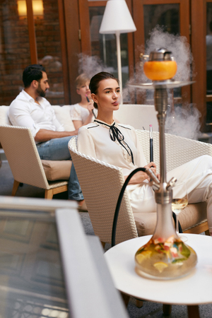 Woman Smoking Shisha In Hookah Bar. Beautiful Fashionable Girl Smoke Fruit Cup Hookah At Luxury Lounge Restaurant. High Resolution Stock Photo