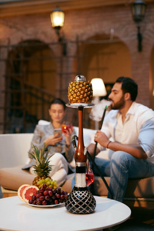 Fruit Shisha In Hookah Bar For Couple. People Smoking Hookah With Fruits, Resting In Luxury Lounge Cafe. High Resolution