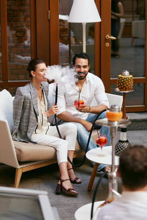 Couple Smoking Shisha And Drinking Cocktails In Hookah Bar. Man And Woman Relaxing In Cafe. High Resolution